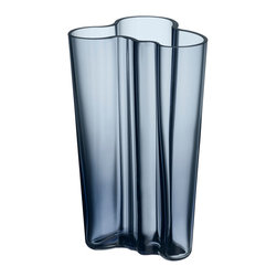 """iittala Aalto Finlandia Vase 7.75"""" Rain - The Aalto Vase is part of the Alvar Aalto Collection for Iittala and is one of the most iconic and enduring pieces of Finnish design. Sometimes called the Savoy Vase because it was designed by Alvar Aalto and his wife Aino Aalto for the Savoy restaurant in Helsinki, Finland, the vase was displayed at the 1937 World's Fair in Paris. The Aalto vase was originally inspired by the hem of a woman's dress of the Sami people, an indigenous people that live in northern Sweden, Finland and Norway."""
