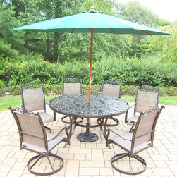 Oakland Living - 9-Pc Outdoor Sling Dinning Set - Includes table, six swivel rockers, 9 ft. umbrella with stand and metal hardware. Traditional lattice pattern and scroll work. Hardened powder coat. Handcast. Fade, chip and crack resistant. Warranty: One year limited. Made from cast aluminum. Coffee color. Minimal assembly required. Table: 60 in. Dia. x 29 in. H (70 lbs.). Swivel Chair: 24 in. W x 30.5 in. D x 40 in. H (16 lbs.)The Oakland cascade collection combines contemporary style and modern designs giving you a rich addition to any outdoor setting. We recommend that the products be covered to protect them when not in use. To preserve the beauty and finish of the metal products, we recommend applying an epoxy clear coat once a year. However, because of the nature of iron it will eventually rust when exposed to the elements.