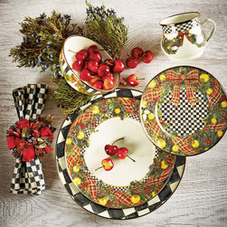 Holiday Entertaining - Lavishly decorated Christmas dinnerware from MacKenzie Childs is adorned with an abundance of greenery, berries, and pine cones amid the signature tartan plaid and Courtly Check® patterns.