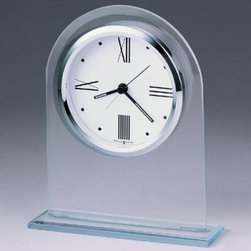 Howard Miller Regent Desktop Clock - The crisp white dial of this alarm clock is suspended within a beveled glass arch mounted on a glass base. A polished silver-tone bezel surrounds the white dial and contemporary Roman numerals and hour markers. Black hands are featured with luminous inserts. Quartz alarm movement includes the battery. There's a certain level of expectation that comes with the Howard Miller name. And then there's the steady stream of surprises that make you stop in your tracks and take a second look. From traditional to hot trends and floor clocks to wine furniture you'll find even more than you expected at Howard Miller. Fine details expert craftsmanship and beautiful materials; no matter what your taste or budget a Howard Miller clock fits the bill.About Howard MillerBeginning in the 1920's Howard Miller clocks have impressed all who see them with superior quality and design. Howard Miller wall floor and mantel clocks are crafted to last for generations and to perfectly accent your home.The company's founder Howard C. Miller began manufacturing wall and mantel clocks in Michigan. Evolving to encompass cabinet making and other furniture design - all renowned for quality and style - the Howard Miller company proudly stands behind its reputation as the World's Largest Clock Manufacturer.