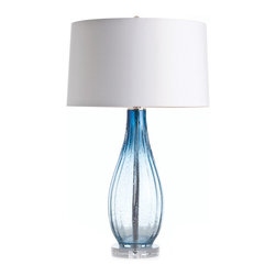 Parkland Blue Optic Glass / Acrylic Lamp - Anyone who appreciates the timeless beauty of sunlight shining through a beautifully shaped vintage glass bottle cannot help but fall in love with the artful Parkland Lamp.  Its fluted base is made from ombre ocean-blue optic glass that sparkles with the prism effect of crystal, enhanced by tiny bubbles caught in the glass for a handmade effect.  The base rests on a small clear acrylic pedestal, improving its transmission of light, and is topped by a white drum shade.