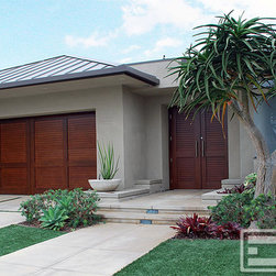 Dynamic Garage Door - Modern Design Garage Door & Matching Courtyard Entry Gate in Solid Mahogany Wood - Designing modern garage doors requires keeping in mind the basics of modern architecture. The trick is to keep clean lines without overdoing the linear repetition. This modern style home was retrofitted with minimalistic designed courtyard gates and overhead garage door. Both, the custom garage door and entry gates, were done in a basic horizontal v-groove design with simple stile and rail trim pieces to frame in the horizontal linear patter while helping break the monotony of the continuous horizontal lines. A contrasting stain was selected to make the cold contemporary look of the house warmer. The doors are hearty and inviting while the stucco and metal roof lines stay true to what simplistic modern design should be. Combining the design of your entry doors and garage doors as a single-time project can prove to be efficient or at least using the same company. In this way, the design transfer from one to the other is swift, elegant and true to the original design concept. Avoid using two different companies when possible. Fortunately, Dynamic Garage Door specializes in designing modern garage doors and entry gates or front door systems. Speak with one of our designers today and see what the difference is when you're not limited to selecting designs from a pre-established brochure and just let your imagination run free. Our best designs are usually a collaboration from our client's unique taste and the creativeness of our in-house designers.