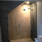 """ATM mirror and glass - Fully Frameless Steam Glass Shower Enclosures - full view of custom fully frameless glass shower enclosure, with interior cut out in fixed panel for operating steam transom. This enclosure features 1/2"""" starphire glass, solid brass construction fittings - plated in polished nickel.  Custom cut angled ceiling.  Door opens in 90 degrees and out 90 degrees. Glass clamp method."""
