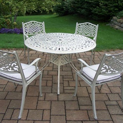 Oakland Living - 5-Pc Traditional Dinning Set - Includes capital table, four chairs with cushions and metal hardware. Lattice pattern and scroll work. Handcast. Hardened powder coat. Fade, chip and crack resistant. Warranty: One year limited. Made from rust free cast aluminum. Beach sand color. Minimal assembly required. Table: 48 in. Dia. x 29 in. H. Chair: 22.5 in. W x 22 in. D x 35 in. H (23 lbs.)The Oakland Mississippi collection combines grace style and modern designs giving you a rich addition to any outdoor setting. We recommend that the products be covered to protect them when not in use. To preserve the beauty and finish of the metal products, we recommend applying an epoxy clear coat once a year. However, because of the nature of iron it will eventually rust when exposed to the elements.