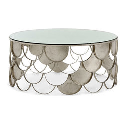 Lira Coffee Table - Eclecticism embodied in a single, unified piece, the Lira Coffee Table is glazed in a metallic champagne which is close to silver, but lightened by a slight touch of warmer antiqued tone. Its scallop-shaped edges suggest lightness, space, and a taste for traditional patterns, while the antiqued mirror top conveys a certain aged splendor to a room.