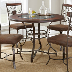 None - Torino 45-inch Round Dining Table - The Torino 45-inch Round Dining Table makes any meal enjoyable with its rich cherry finish and decorative beveled glass inlay with intricate metal scrollwork beneath. This table is the perfect size for a breakfast nook or small dining area.