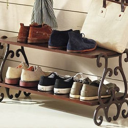 """Moran Shoe Rack - Graceful scrolls of wrought iron, paired with richly stained mahogany, create a functional storage piece that looks anything but utilitarian. This shoe rack organizes shoes and boots in a space-saving two-tier design. 31"""" wide x 14"""" deep x 16"""" high Made of mango wood and aluminum metal with a blackened finish. Catalog / Internet only."""