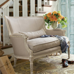 Isla Settee - A delicately carved oak frame is upholstered in a soft viscose/linen fabric to create a piece that exudes classic elegance and comfort. The down-wrapped cushion is under-stuffed, giving it a relaxed look. This beautiful settee is the perfect perch for your guests at your next gathering.