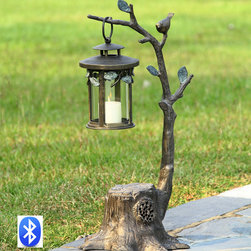 "Bird on Branch Lantern with Speakers - More than a fanciful rendition of a faux bois twiggy tree, our patio accent provides light from the swinging lantern and plays music from your cellphone or other bluetooth device. Connects easily to any bluetooth unit. Loud & clear, 10 watt speaker hidden inside the base. Dimensions: 17""w x 16.5""d x 31.5""h"