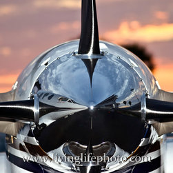 Airplane at Sunset - Reflection of airplane and airport terminal in the background is reflected in the nose cone of this Beechcraft King Air turboprop aircraft. Beautiful orange sunset makes a great backdrop.
