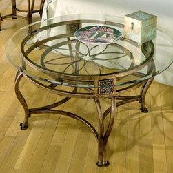 Hillsdale Furniture - Round Cocktail Table w Floral Motif Iron Fram - Enjoy the beauty of a themed cocktail table from above or from the sides. A floral motif is crafted with intricate wrought iron shaping at the hub of the frame. Apron features matching artisan crafted insets topping the bowed legs. * For residential use. This exquisite table features graceful flowing lines and intricate castings. The most stunning effect, however, is the flower motif and lovely brown rust finish that lies beneath the clear glass top. Brown rust finish. Floral motif. Some assembly may be required. Table: 28 in. W x 17.5 in. H x 28 in. D. Glass Top Diameter: 39 in.
