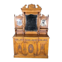 """Pre-owned English Antique Server with Hutch - This stunning English antique is a solid oak buffet sideboard dating back to 1890-1910. It features a breathtaking pediment at top and a stunning hutch that includes 1 large/2 small armor shaped beveled mirrors, carved floral accents, 2 convenient shelves with acanthus leaves, lovely finials and reeded accents. In addition there are a total of 3 spacious cabinets that all have shelves inside. There are 3 smooth operating felt lined drawers with dovetail joinery, traditional facings with beautiful brass handles and hardware. This piece may show minor age appropriate signs of wear otherwise - as shown - it is in overall excellent condition both cosmetically and structurally. Very strong and sturdy. This is a gorgeous piece of furniture that will not only enrich your home decor with its presence but will also become a treasured heirloom in your family!    ITEM DESCRIPTION:  Country of Origin: England  Circa: 1890-1900  Solid Oak Construction  Victorian Style  Carved Pediment  Foliage, Floral & Scroll Carvings  2 Top Shelves  1 Large Beveled Mirror  2 Side Beveled Mirrors  Paneled Hand Carved Surfaces  3 Felt Lined Drawers  Dovetail Joinery  Fancy Brass Handles & Hardware  3 Cabinets with shelving inside  Paneled Doors w/ Carvings  Reeded Accents  Excellent Condition!  Very Clean, Strong & Sturdy    DIMENSIONS:  89H x 60W x 22D   (Height from floor to buffet is 39"""")"""