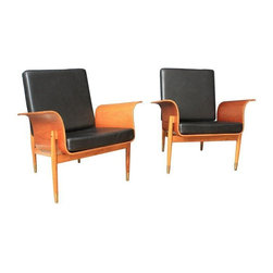 Used Mid-Century Modern Lounge Chairs - A Pair - This is a pair of vintage Mid-Century bent wood lounge chairs. A continuous piece of wood rolls from one armrest, under the seat, to the second armrest - a groovy design! Great condition with vintage wear such as scratches on the wood frame.  The cushions are new and have been upholstered in black leather.