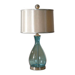 Uttermost - Meena Blue Glass Table Lamp - Gleaming from stem to stern, this stunning lamp will reflect the light so beautifully in your home. With a clear blue mouthblown glass base and satin nickel accents, this lamp stands a cut above the rest. The silken silvery gray round hardback shade is the perfect compliment to the blue body, making this a truly gorgeous lamp for your side table.