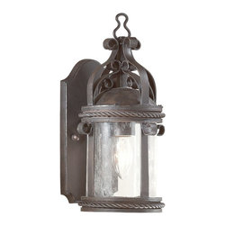 "Troy - Country - Cottage Pamplona Collection 12 1/4"" High Outdoor Wall Light - This wall light was inspired by antique outdoor fixtures seen in the sun drenched Spanish city of Pamplona. The handsome design includes accent ribbon scrolls clear seeded glass and a hand forged iron frame. Rope braid trim accents the glass. Old bronze finish. Takes one 100 watt bulb (not included). 12 1/4"" high. 6"" wide. Extends 7"" from the wall.  Old bronze finish.  From the Troy Lighting outdoor wall light collection.  Takes one 100 watt bulb (not included).  12 1/4"" high.   6"" wide.   Extends 7"" from the wall."