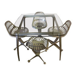 """Pre-owned Azcast Aluminum Dining Set - Azcast aluminum dining set with glass top and tractor seat chairs. All Azcast products are made from recycled aluminum. Table measures 40"""" x 40"""" x 30"""" h. In great condition, no chips on glass. This set is perfectly contemporary yet industrial and rustic. We think it'd look amazing pair with an exposed brick wall or concrete floors!"""