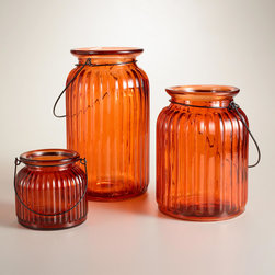 World Market - Orange Ribbed Glass Lantern Candleholder - This unique Orange Ribbed Glass Lantern Candleholder is crafted specially for us in a spectrum of brilliant shades. Inspired by historic glass lamps, this lantern holds a pillar candle and looks lovely atop tables or hanging from its rustic metal handle.