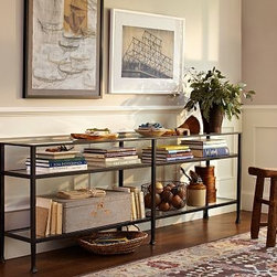 "Tanner Long Console Table with Glass Top - Perfect for showcasing collectibles or displaying books, this updated version of our popular console features the same streamlined shape in a substantial extended profile. Each piece in our Tanner collection has hand-hammered iron frames inset with tempered glass. 65"" wide x 14"" deep x 30.5"" high Frame is crafted of forged wrought iron for strength. Shelf is crafted of tempered glass for safety. View our {{link path='pages/popups/fb-media.html' class='popup' width='480' height='300'}}Furniture Brochure{{/link}}."