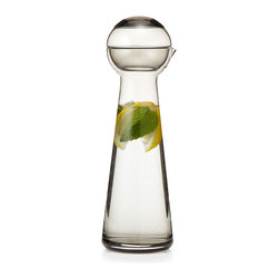 """Modern Glass Carafe - The phrase """"as the crow flies"""" sets your mind to stripping away all unnecessary details until you get down to the simplest truth. So it's appropriate that a bird was designer Markus Johansson's inspiration for this minimalist carafe. It reduces the bird's form down to geometric elements--a cone-shaped vessel and a spherical stopper. It's the tiny, beak-like stopper that catches your imagination and allows you to see the form for what it is. Appropriate for water by your bedside, juice with brunch, or dispensing your favorite, prized spirit."""