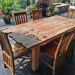 Reclaimed Teak Dining Tables - A very rustic teak dining table and chairs made from reclaimed old growth teak railroad ties / trestle bridge pieces.  Can be used indoors or outdoors.  The sun will bleach all wood, but the old growth teak is great for outdoor use!  Impact Imports can make a custom teak table for you!