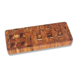 """Bambeco Teak Serving Board - This stunning end-grain Teak Serving Board is perfect for chopping and serving. The gorgeous grain of teak shows through in this practical piece. Cut-out handgrips on either end make lifting and moving the board a snap. These beautiful pieces are crafted from conflict-free, FSC-certified organic teak grown on a sustainably-managed, renewable plantation located on reclaimed ranch lands. Teak has long been prized in the marine industry, and those same features make it ideal for cutting boards. The high levels of natural oils help repel moisture and prevent the wood from warping or drying out.  Care: Hand wash with mild soap and water, allow to dry thoroughly. Periodically treat with a light, food-grade oil to preserve the wood's natural beauty and prolong its life. Dimensions: 18""""L x 6""""W x 2""""H"""