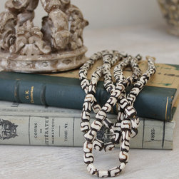 Small Cow Bone Beads - Though they are carved from bone, these pale chalk-white rondelle beads look as though they might be hand-rolled in unfinished pottery with their matte finish and slight irregularities of shape and size. �This knotted strand can be put to dozens of uses in the home, bringing an African-import flavor in blending neutral colors to your decor. �A perfect transitional accessory, they're superb for easing the formality of a stiff vignette with a more natural spontaneity.