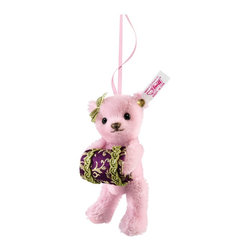 Emma Teddy Bear Ornament EAN 034831 - Do you hear the sound of sleigh bells? Do you feel the crunch of snow underfoot? If so, it's time to celebrate the season with our Teddy bear Emma ornament. She's the perfect addition to any Christmas tree. Emma stays warm in her pale pink mohair coat while nestling her hands in a handmade Jacquard muff. Her shiny black eyes reflect the light of the bright winter snow. In her hair, Emma wears a tiny golden bow that's perfect for the festive atmosphere of the holidays. Invite Emma to your yule-tide celebrations and watch her spread good cheer.