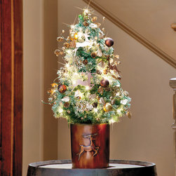 Frosted Leaping Reindeer Tabletop Christmas Tree - 1-Gallon - The leaping reindeer on the embossed, copper-finished cachepot and the Dwarf Alberta Spruce tree will grab the kids' attention, holding the promise of a visit from St. Nicholas! And every adult will love the gold- and copper-colored ornamental balls, cone and berry garland, punched metal snowflake ornaments, snowflake topper, and sparkling white lights, which make it an elegant addition to any room!