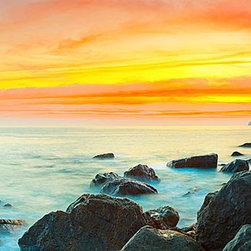 Magic Murals - Rocky Shore Sunset Panorama Wall Mural -- Self-Adhesive Wallpaper by MagicMurals - This panoramic seascape captures a vibrant sunset off the Pacific Ocean.  Gold and pink skies, blue sea waters shrouded in mist and rocky shore being crashed by waves.