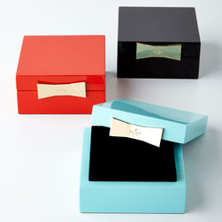 """kate spade new york - Garden Drive Jewelry Box - kate spade new yorkGarden Drive Jewelry BoxDetailsLacquered box has flocked interior.Select color when ordering.Golden metal clasp.Lid lifts off.4""""Sq. x 2""""T.Imported.Designer About kate spade new york:In 1993 former magazine accessories editor Kate Brosnahan created a sleek black handbag under the label kate spade new york that became famous around the world. In 2007 Deborah Lloyd formerly of Banana Republic and Burberry took the helm as president and chief creative officer with an aim to broaden the line while honoring its history. Craig A. Leavitt joined shortly thereafter to realize the global potential of the brand that now has dozens of retail shops a thriving e-commerce business and boutiques around the world and has grown to include shoes jewelry fragrance eyewear hosiery tabletop paper and women's ready-to-wear."""