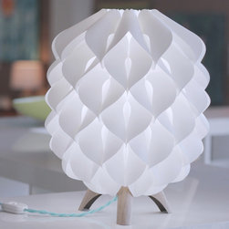 Lightology Collection - Blom Table Lamp - The shape of the Blom table lamp relies on the subtle interaction between its leaf-like parts, the way a flower is formed by its petals. Its design is inspired by the process of growth, which underlies the emergence of shapes in nature. Traces of this approach can even be found in the striking grain pattern on the legs.  A cloth covered cord provides a splash of color and a hint of nostalgia. The modernist design of the Rompitratta in line switch is by legendary Italian designer Achille Castiglioni.  Shade made of white high density polyethylene.  Available in Dark wood with Red cord or Light wood with Teal cord.  One 40 watt, 120 volt A19/Medium base Incandescent bulb is required, but not included.  Dimensions:  11 inch width x 14 inch height.  Some assembly required.