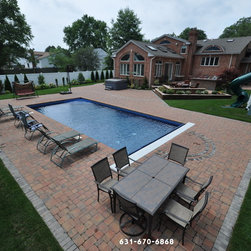 Pool Pavers - Patio Furniture Long island NY - In this photo we see a beautiful clean cut patio made in Autumn Blend Pavers in Bellport NY  11713 The grey pavers out lining the patio bring out the grey in the autumn blend pavers and add to that clean cut look. We also see multiple different types of outdoor furniture such as a table & chairs to have dinner or lunch outside on the warm summer months and also lounge chairs to catch some rays. The landscaping outlining the backyard really pops against the white PVC fencing that surrounds the yard, and gives the backyard some color which makes it seem very inviting. The main attraction of this backyard is the vinyl in ground swimming pool with an automatic pool cover which makes your pool ready at any time to be used when having any guests over in the summer months.