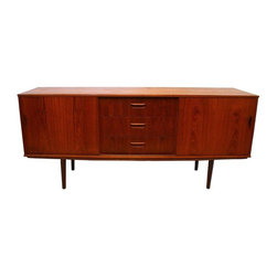 Used Danish Modern Sideboard Credenza - A great quality Mid-Century Modern teak wood sideboard attributed to the designs of Arne Vodder, and Clausen and Son. The credenza is marked, made in Denmark. Beautifully rich in color, this cabinet includes two bottom sliding doors with 3 center drawers. It is in great condition with minor wear. This piece is beautiful and would be a great addition to any Mid-Century or Danish Modern décor.