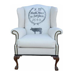 Vintage Wing Chair - This solid wood, carved claw foot wing chair features an authentic German grain sack with a marvelous wreath and cow graphic with the original drawstring to the sack.