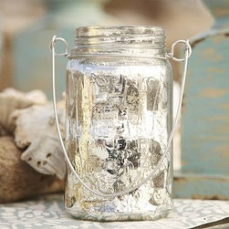 """Mercury Glass Hanging Mason Jar Candle Holder - Hang several of these lanterns around an outdoor garden or patio for casual and inviting lighting. An antique mercury finish adds a shimmering glow. Jar: 3.5"""" diameter, 6"""" high Made of blown glass with an antiqued mercury finish. Aluminum wire handle."""