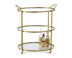 Connaught Bar Cart - Antique Brass - A useful element for the dining room, bar, or bath with a light, space-saving triple design, the oval Connaught Bar Cart has a warm brass frame, simply designed for a sleek look but given classical gravitas with fluted uprights. Each oblong glass shelf holds its share of dishes or bottles, providing open storage and attractive display on convenient decorative casters.
