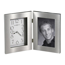Howard Miller - Lewiston Table Top Clock with Silver-Tone Fra - Keepsake clock and picture frame is the perfect addition to your desktop. It features a swirling brushed silver finish to accentuate your contemporary style. Hinged clock has a white dial with black numbers that are easy to see. The other side is home to a favorite 4 x 6 photograph. A frame with swirling brushed silver finish surrounds the dial and picture window of this hinged, tabletop clock. The dial is white with black Arabic numerals, black minute and second hands, and a silver second hand. Picture frame holds a standard 4 in. x 6 in. photo. Quartz movement includes the battery. 11 in. W x 1 1/2 in D x 7 1/2 in. H