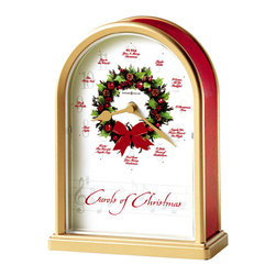 """Howard Miller - Musical Carols of Christmas Mantel Clock - HO HO HO. The holiday season is always at hand. Get a step ahead when you order this charming holiday timepiece and create a jolly holly holiday for yourself. Golden hands combine with combinations of red gold and green easily to celebrate the holiday. * The acrylic crystal protects the dial and the gold tone hour and minute hands. . Automatic nighttime chime shut-off option. . Quartz movement includes battery. . H. 7-1/2"""" (19 cm). W. 5-1/2"""" (14 cm) . D. 2-1/2"""" (6 cm)As the hour hand moves from hour to hour, you'll hear these carols featured at the hour: (1) Jingle Bells, (2) O Come All Ye Faithful, (3) O Christmas Tree, (4) Angels We Have Heard on High, (5) O Little Town of Bethlehem, (6) God Rest You Merry Gentlemen, (7) Hark! The Herald Angels Sing, (8) Silent Night, (9) Deck the Halls, (10) The First Noel, (11) Joy to the World, (12) We Wish You a Merry Christmas.. This satin brass finished table clock features red marble-tone sides and a decorative wreath at the center of the dial.. This original, signed artwork was commissioned by Howard Miller exclusively for the Sounds of the Season Collection."""