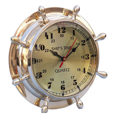 """Handcrafted Model Ships - Brass Double Dial Porthole Wheel Clock 8"""" Brass Desk Clocks Brass Clock - New - The Hampton Nautical Double Dial Wheel Clock is a solid brass desk clock. This brand new antiqued ship wheel clock is a perfect accent to any home, office or study. This clock features both the 12-hour and 24-hour marks and has 1 minute interval marks. Inside the clock the words """"Ship's Time"""" in an elegant font is displayed. The back features a groove to hang this clock on a wall."""