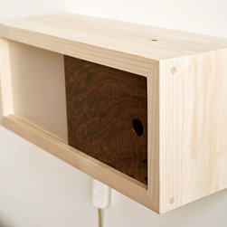 LightBox - LightBox is a simple and modern bedside light that adds a perfectly warm and pleasant night time light, with an extra sliding door for any bedroom necessities. Made of Port Orford Cedar, this lightbox has a beautiful aromatic wood smell.  A dimmer switch controls brightness, and it can even be used as a mini bookshelf!