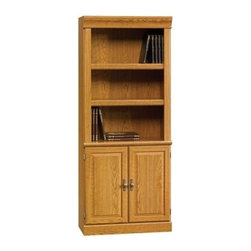 Sauder - Orchard Hills 2 Door Bookcase in Carolina Oak - 3 Shelves. Hidden storage behind raised panel doors. Enclosed back panel has cord access. Patented slide-on moldings. Made of engineered wood. Assembly required. 29 in. W x 13 in. D x 71 in. H