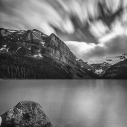 """Falling Sky"" Artwork - This photograph was taken in lake louis, which is located in banff national park. the lake was calm while the clouds moved swiftly across the sky. this image was created using a longer exposure in the camera. the mountains have snow on them while the trees at the lower elevation absent of the white powder. all images are available in the following sizes: 13x19 unframed on luster photographic paper - 17x25 unframed on luster photographic paper - 20x30 printed on metallic and mounted on plexiglass -$1100 limited to 9 artist proof editions in a particular size. they will be signed and numbered on the back of the image. i print all images using the latest technology, the highest-quality papers, and newest archival inks. additionally, i include a 5mm white border to ensure proper handling that eliminates the potential for fingerprints."