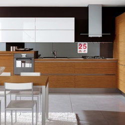 "Designer Range Hoods - ""Loft CTM"" Series - The ""Loft CTM"" designer range hood from Futuro Futuro is equipped with a removable bottom portion that allows the installation of a custom shelf or panel. In this example, a short stainless-steel panel emphasizes the horizontal lines of the cabinetry."