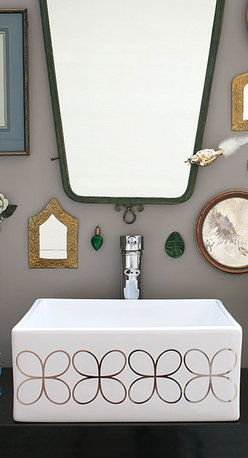 """Platinum Cloverleaf Design Hand Painted Sink - Cloverleaf design hand painted sink in platinum on a white square vessel sink. 16"""" x 16"""" diameter, material vitreous china. Shown in a gray bathroom with vintage mirror collection, clocks and curios."""
