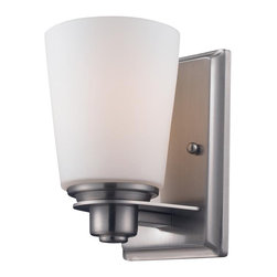 One Light Brushed Nickel Matte Opal Glass Bathroom Sconce - Straight contemporary lines and a contrasting cone shade create a straight contemporary look. This wall sconce is finished in satin nickel, and includes a matte opal shade. This fixture will add a touch of contemporary to any decor.