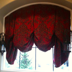 Custom Top Treatments - This is truly a special window treatment.  The planning and construction took time as typically treatments like these do not function.  We actually created a way for this client to partially lower and raise their new gorgeous roman shade over their kitchen sink.