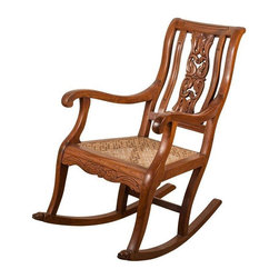 Used Teak Rocking Chair from 19th C. India - Indo-Portuguese rocking chair in solid teak with carved back and front stretcher. Dog heads carved on front of legs. From the late 19th century, India. Newly caned seat.