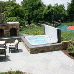 Spa Outdoor Spaces - A HotSpring Spa could be the perfect addition to your outdoor patio. Enclosed in a beautiful stone wall, this HotSpring Grandee in Coastal Gray with a gray cover fits perfectly with this outdoor living space.