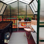 Grow N Up 8' x 10' Hobby Greenhouses - This is the Grow N Up 8' x 10' Hobby Greenhouse Kit from EarthCare Greenhouses, the photograph was taken by a customer. The customer built the red wooden base with steps, for the foundation of the greenhouse. The kit does not require a base.