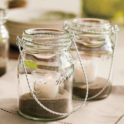 Hanging Mason Jar - Hanging Mason jars with candles inside is another fun way to add soft light to an outdoor entertaining space. I would love to see these clustered together and hanging in a tree.